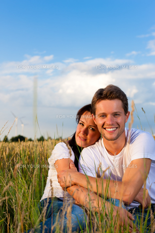 happy couple sitting on a meadow or field of cornの写真素材 [FYI00837567]