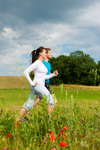 young sporty couple jogging outdoorsの写真素材 [FYI00837603]
