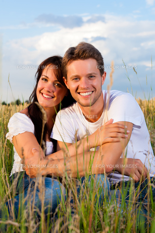 happy couple sitting on a meadow or field of cornの写真素材 [FYI00837605]
