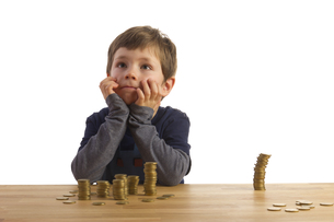 a boy sitting in front of several vert?umt money stacksの素材 [FYI00838535]