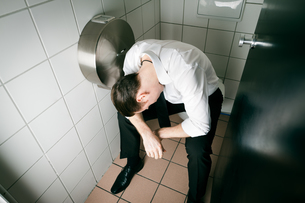 young drunk man sleeping on toiletの写真素材 [FYI00840091]