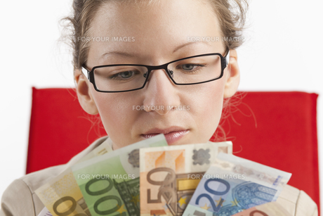 young woman looks at subjects from banknotesの素材 [FYI00840578]
