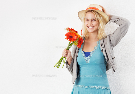 happy woman with sun hat and bouquet of flowersの写真素材 [FYI00841653]
