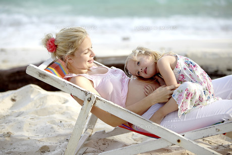 young pregnant mother sitting with her daughter in deckchair onの写真素材 [FYI00842580]