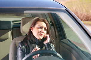 young woman with cigarette and mobile phone in the carの写真素材 [FYI00842932]