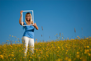 young woman with picture frame in natureの写真素材 [FYI00843665]