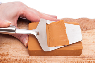 hand cheese with cheese slicer does planingの写真素材 [FYI00844025]