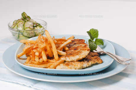 fish fillet with fries on blue plateの素材 [FYI00846007]