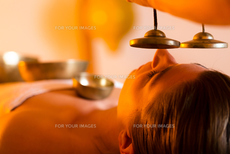 woman in wellness and singing bowls massageの写真素材 [FYI00846417]