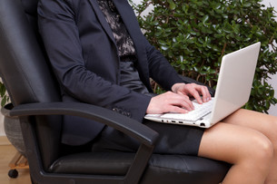 young businesswoman with a notebook on her knees on workingの素材 [FYI00846727]
