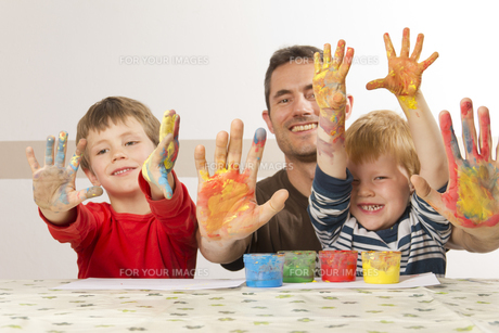 father paints with his children with finger paintの素材 [FYI00847139]