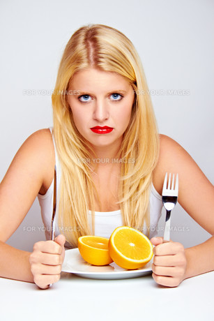 unhappy young woman eating fruit with silverwareの写真素材 [FYI00847265]