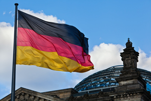 dome of the german reichstag in berlin with germany flagの写真素材 [FYI00848181]
