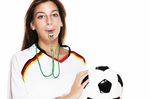 young woman with a whistle holding footballの写真素材 [FYI00848322]