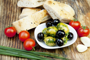 green olives with fresh bread and herbs on a holzbretの写真素材 [FYI00848425]