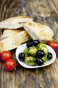 green olives with fresh bread and herbs on a holzbretの写真素材 [FYI00848433]