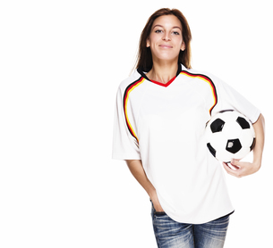 laughing young woman in football shirt with football under his armの写真素材 [FYI00848438]