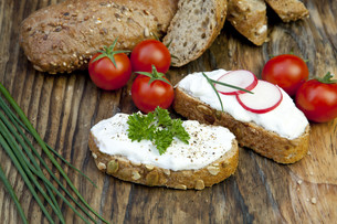fresh bread with herb quark and tomatoes for a snack on eggの写真素材 [FYI00848455]