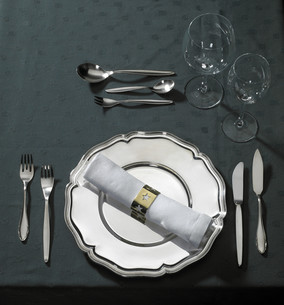 feastful place setting on green tableclothの写真素材 [FYI00850982]