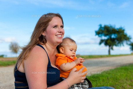 family - mother and child sitting in a meadowの写真素材 [FYI00853448]