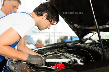 customer and mechanic at car look under the hoodの写真素材 [FYI00854638]