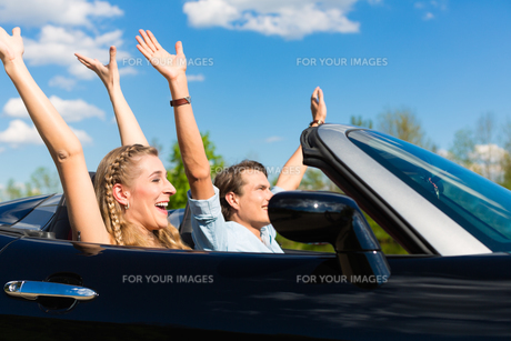 young couple with cabriolet in summer on a tripの写真素材 [FYI00854656]