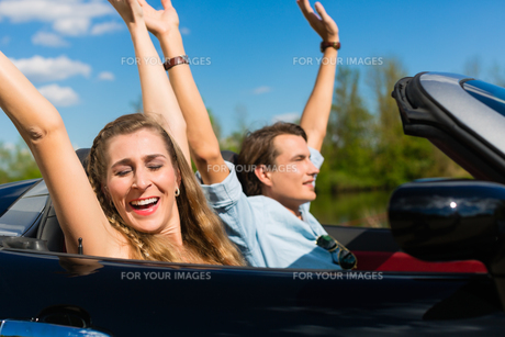 young couple with cabriolet in summer on a tripの写真素材 [FYI00854746]