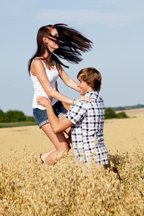 happy amorous couple in cornfield in summer outdoorsの写真素材 [FYI00856789]