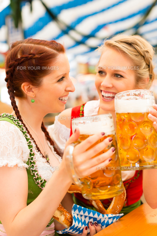 young women in traditional dirndl in a beer tentの写真素材 [FYI00857680]