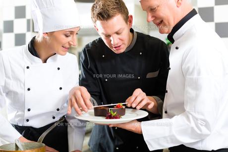 team of chefs with dessert in kitchenの写真素材 [FYI00857684]