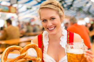 young woman in traditional dirndl in a beer tentの写真素材 [FYI00857686]