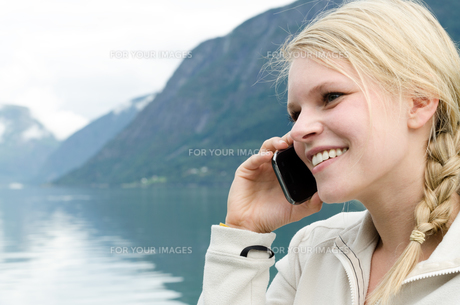 young blond woman on the phone with her smartphoneの写真素材 [FYI00858081]