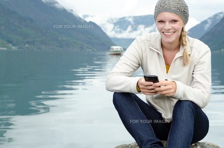 young blonde woman with her smartphone in handの写真素材 [FYI00858127]