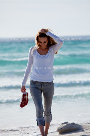 young pretty woman walking on the beach in the sand outdoors in sommの写真素材 [FYI00859044]