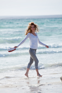 young pretty woman walking on the beach in the sand outdoors in sommの写真素材 [FYI00859084]