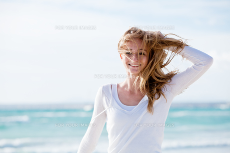 young pretty woman walking on the beach in the sand outdoors in sommの写真素材 [FYI00859109]