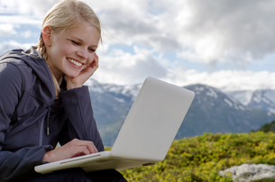young blonde woman with laptop in front of mountain landscapeの写真素材 [FYI00859671]