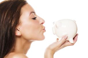 beautiful young woman kissing piggy bankの写真素材 [FYI00859958]