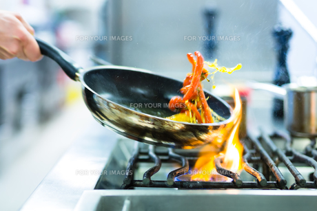 cooking in restaurant kitchen at the stove with panの写真素材 [FYI00862077]