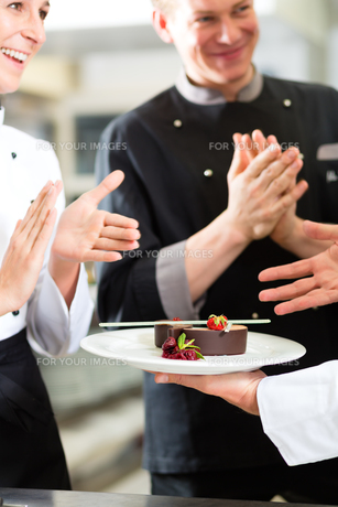 team of chefs with dessert in kitchenの写真素材 [FYI00866002]