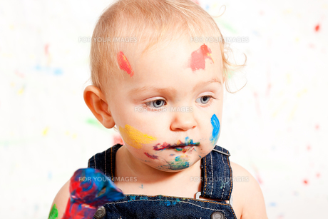 sweet little child in overalls with brushes and colorsの写真素材 [FYI00866240]