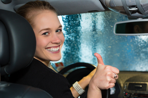 young woman driving a car in car washの写真素材 [FYI00866484]