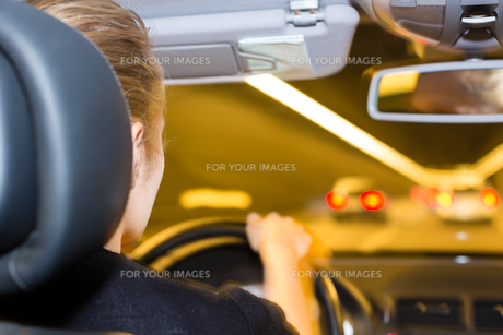 young woman driving a car in the tunnel on highwayの写真素材 [FYI00866497]