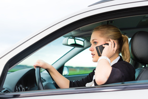 young woman with phone in carの写真素材 [FYI00866517]