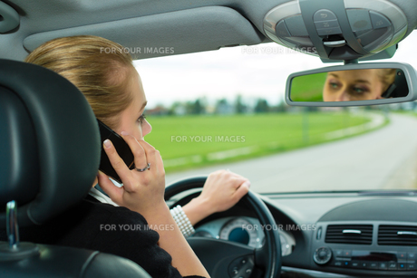 young woman with phone in carの写真素材 [FYI00866543]