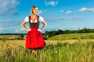 young woman on the meadow and carries dirndlの写真素材 [FYI00867032]