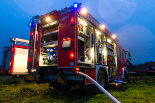 firefighters in action with blue lightの写真素材 [FYI00867033]