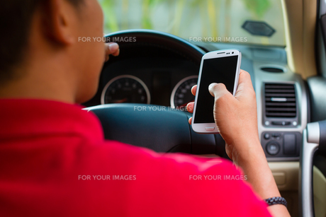 asian man writing sms while drivingの写真素材 [FYI00867042]