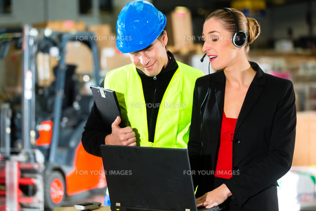 colleagues in the warehouse of a freight forwarder by laptopの写真素材 [FYI00867153]