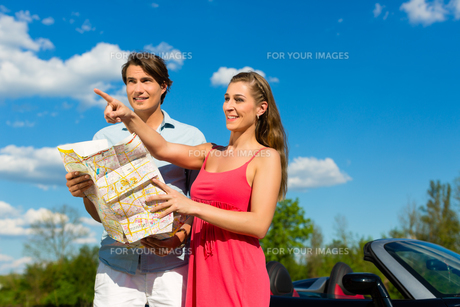 young couple with cabriolet in summer on a tripの写真素材 [FYI00867919]